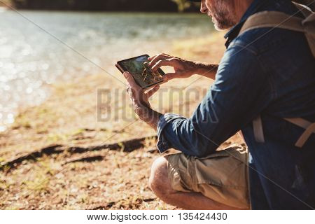 Mature Man On Hike Using A Tab For Navigation