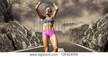 Low angle view of sportswoman celebrating her victory against dark road landscape