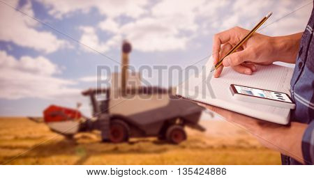 Cropped image of man writing on diary with pencil against view of a harvester
