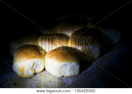 bread rolls at the butter in twilight lit by a grazing light