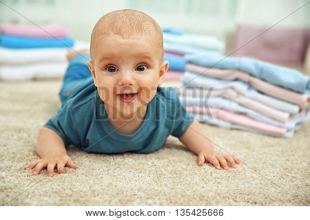 Smiling adorable baby with pile of clothes on the floor