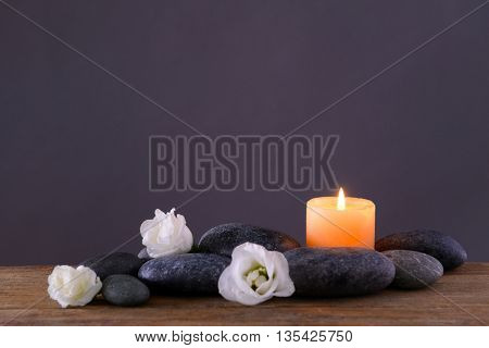 Spa stones with burning candle and flowers on grey background