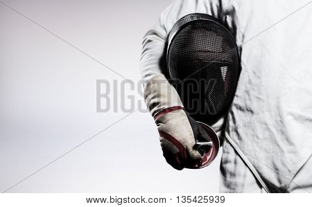 Mid-section of man standing with fencing mask against grey background