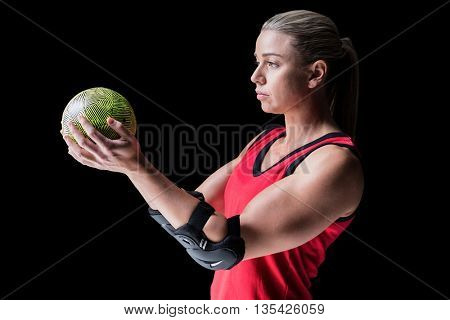 Female athlete with elbow pad holding handball on black background