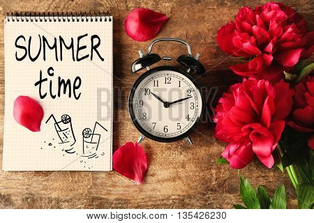 Vintage clock, peony flowers and notebook with text Summer time on wooden background