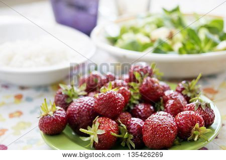 fresh organic strawberries in a green dish