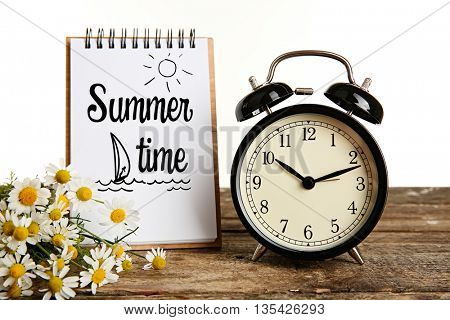 Vintage clock, notebook with text Summer time and bouquet of daisy flowers on wooden table