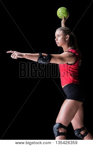 Female athlete with elbow pad throwing handball on black background