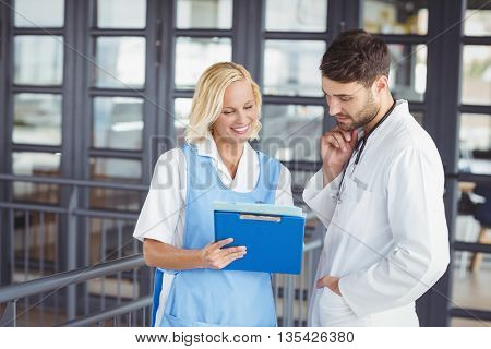 Female doctor discussing with male colleague at hospital