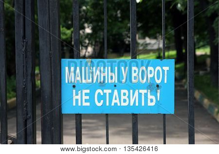 blue sign with warn inscription Do not parking cars at the gates! in street of Moscow
