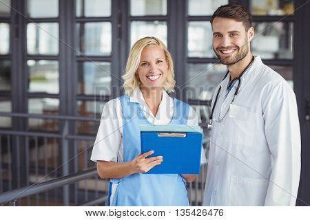 Portrait of cheerful doctors holding clipboard while standing in hospital