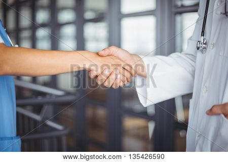 Midsection of doctors handshaking at hospital