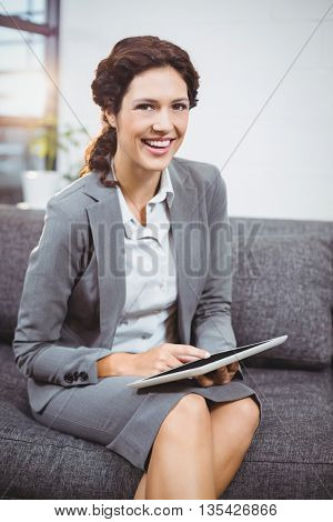 Portrait of cheerful businesswoman using digital tablet while sitting on sofa at office