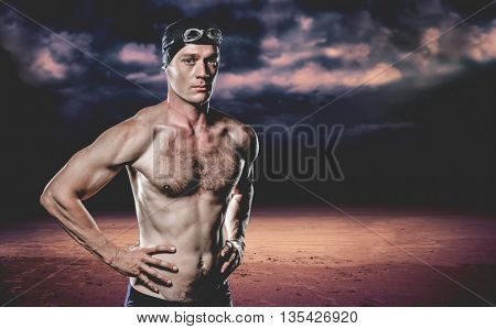 Swimmer standing with hand on hip against dark cloudy sky