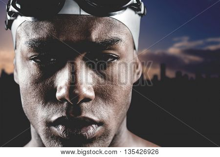 Portrait of swimmer in swimming goggles and swimming cap against picture of a city by sunrise