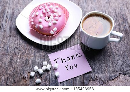 Cup of coffee, doughnut, marshmallows and piece of paper with text Thank You on wooden background