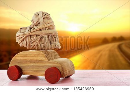 Wooden car with a wicker heart on sunset and road background