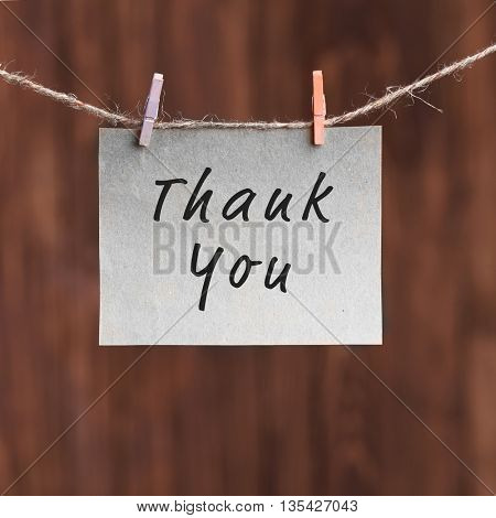 Paper note with text Thank You, on wooden background