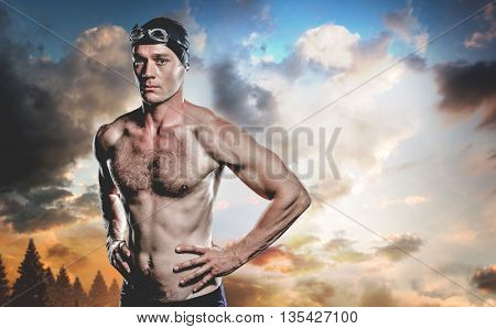 Swimmer standing with hand on hip against country scene