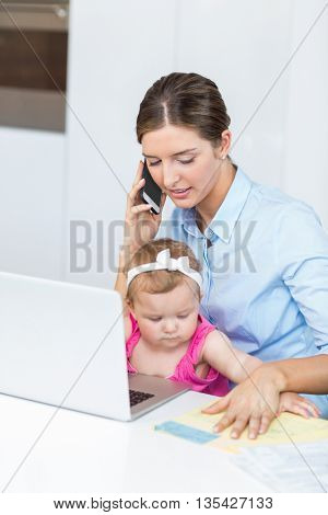 Woman talking on mobile phone while sitting with baby girl by laptop at home