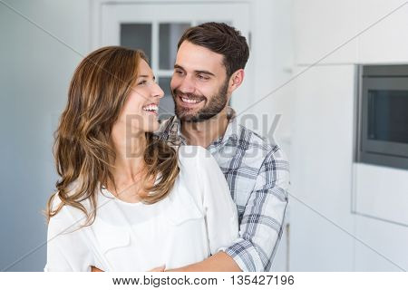 Close-up of happy young couple embracing at home