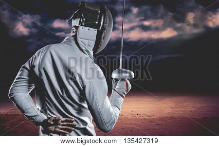 Man wearing fencing suit practicing with sword against dark cloudy sky