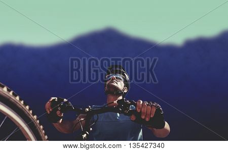 Man cycling with mountain bike against blurred mountains