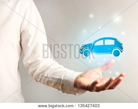 Businessman holding virtual car on grey background