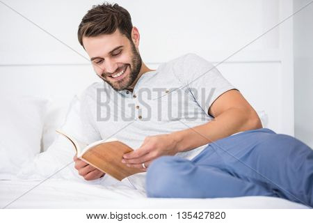 Man smiling while reading book on bed at home