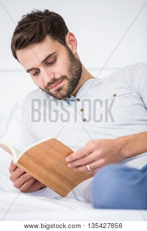 Close-up of man reading book on bed at home