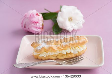 Eclairs with buttercream filling and powdered sugar