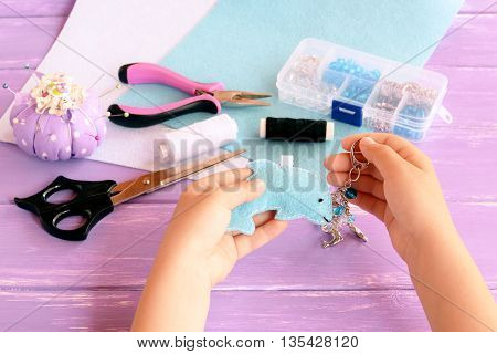 Child holds a dolphin in his hands. Home felt keychain with beads. Pincushion, thread, needles, pins, scissors, pliers, felt sheets, box of beads. Children summer crafts concept