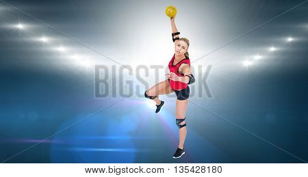 Female athlete throwing handball against spotlights
