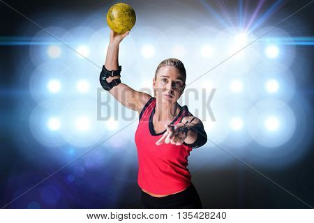Female athlete with elbow pad throwing handball against spotlights