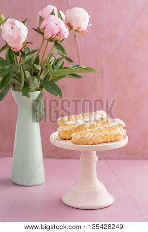 Eclairs with buttercream filling on a pink cake stand