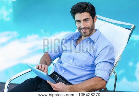 Portrait of smart man relaxing on sun lounger and using a digital tablet near the pool