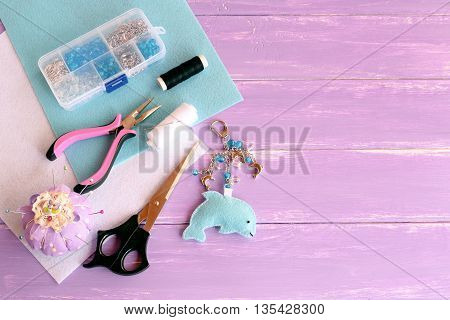 Funny felt dolphin keychain. Home felt plush keychain, bag decor. Handmade car keyring. A set of tools and materials for children's craft and sewing. Lilac wooden background with empty place for text