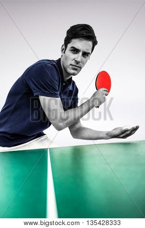 Confident male athlete playing table tennis against grey background