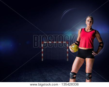 Female athlete with elbow pad holding handball against view of lighting