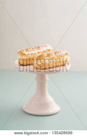 Eclairs with buttercream filling on a cake stand