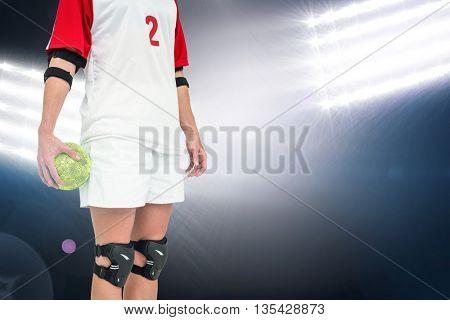 Sportswoman holding a ball against spotlights
