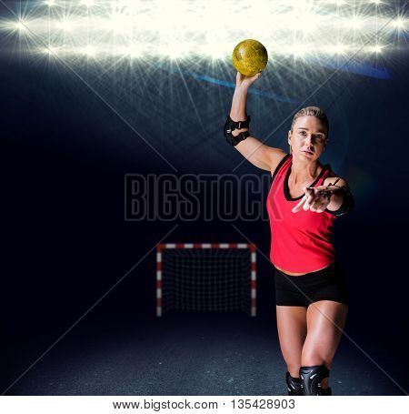 Female athlete with elbow pad throwing handball against view of spotlights