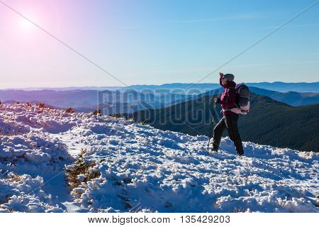 Woman Hiker walking up on snowy Winter Mountain Slope with Backpack and trekking Poles watching further Way to Summit