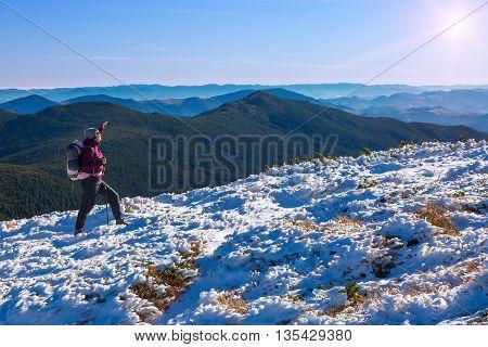 Female Athlete Sport Clothing carrying Backpack Walking Up Mountain Peaks Sunlight Sky Majestic Summits Sun Shining Background