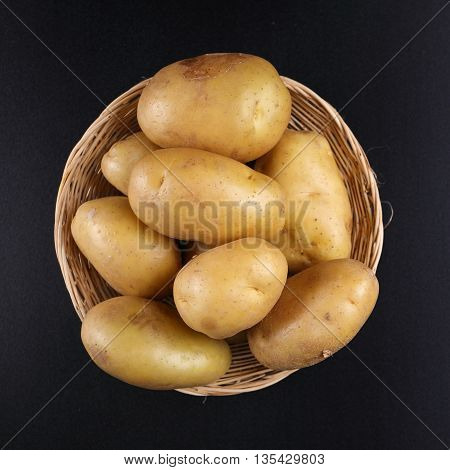 Top view Potatoes in basket on black background