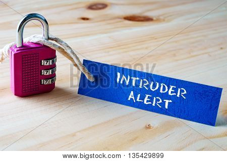 Words Intruder Alert Written On Tag Label Tied With A Padlock.