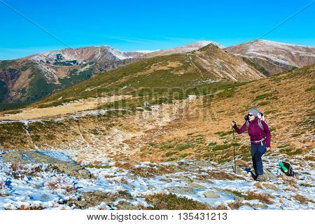 Female Hiker with Backpack and Trekking Pole Walking on Pathway in Winter Snowbound Trail Mountain Landscape Outdoor Sunny Day