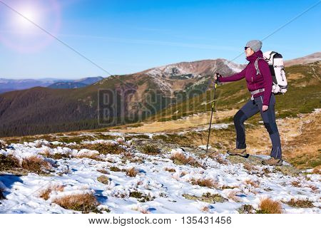Woman Hiker walking up on snowy Winter Mountain Slope with Backpack and trekking Poles watching further Way to Summit Sun Shining from Clear Blue Sky