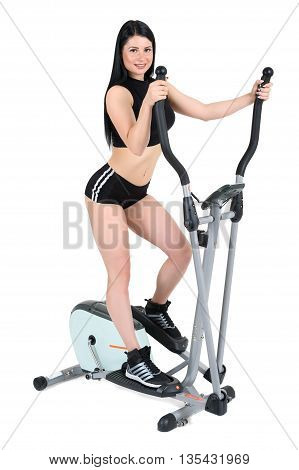 young woman doing exercises with elliptical cross trainer, isolated on white background