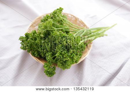 Fresh green parsley in a basket on a white cloth .